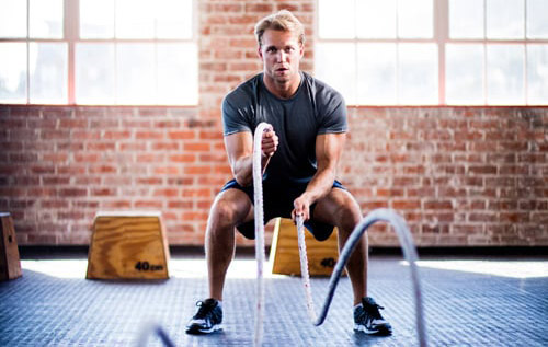 man using battle ropes